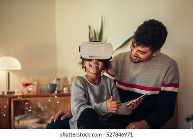 Cute african american girl trying VR glasses at home.