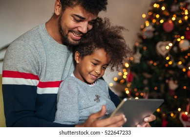 Cute african american girl using tablet with dad at home.