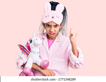 Cute african american girl wearing sleep mask and pajama holding pink teddy unicorn annoyed and frustrated shouting with anger, yelling crazy with anger and hand raised