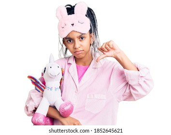 Cute african american girl wearing sleep mask and pajama holding pink teddy unicorn with angry face, negative sign showing dislike with thumbs down, rejection concept