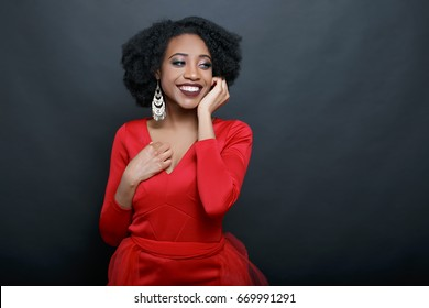 Cute African American in a red dress on a dark background
