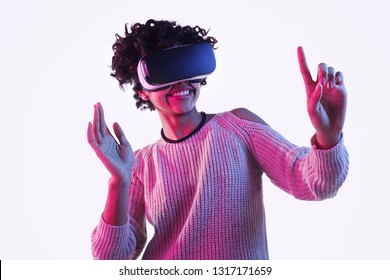 Cute African American teen girl smiling and interacting with invisible screen while having virtual reality experience on white background