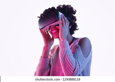 Cute African American teenager smiling and looking away while wearing modern VR headset and standing on white background