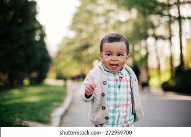 Cute african american toddler having fun outdoors in park.