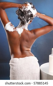 Cute African American washes her hair and turns her back to the camera