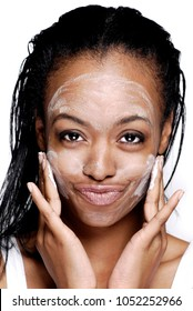 Cute African American woman applying cold cream to her face