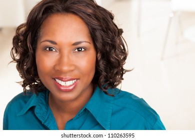Cute African American woman with dark brown hair wearing a blue shirt.
