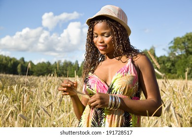 Cute African American woman smiling in a wheat field.