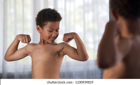 Cute african boy showing arm muscles in front mirror, sport power, health care