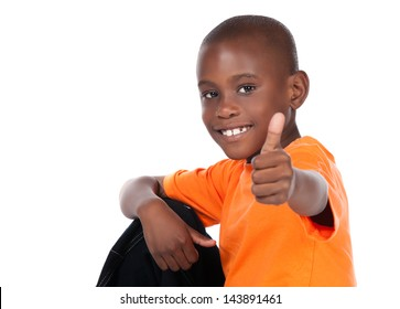 Cute african boy wearing a bright orange t-shirt and dark denim jeans. The boy is showing a thumbs up to the camera.