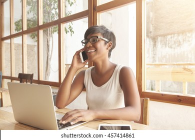 Cute African female student with short stylish haircut sitting at a cafeteria shopping online using notebook, talking to her friend on cell phone, laughing, wearing glasses, looking carefree and happy