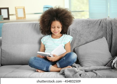 Cute African girl reading book on couch