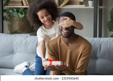 Cute african kid daughter closing eyes congratulating black dad with happy birthday giving gift box sitting on sofa, child girl making surprise preparing present on fathers day having fun with daddy