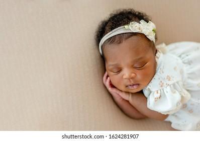 Cute African newborn baby sleeping head on her hands