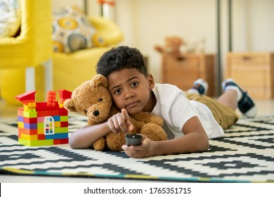 Cute African preschooler with remote control and brown teddybear pointing at you while lying on the floor of living-room