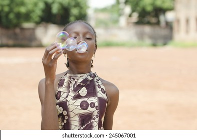Cute African Schoolgirl Playing Fun Games Blowing Soap Bubbles