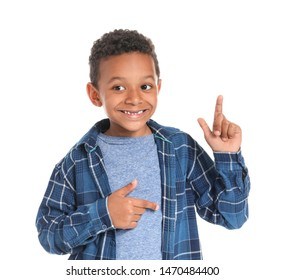Cute African-American boy pointing at something on white background