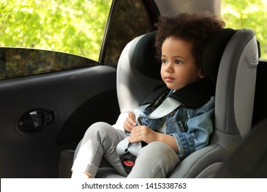 Cute African-American child sitting in safety seat inside car. Danger prevention