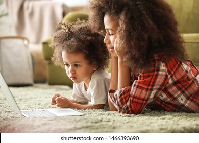 Cute African-American sisters with laptop watching cartoons at home
