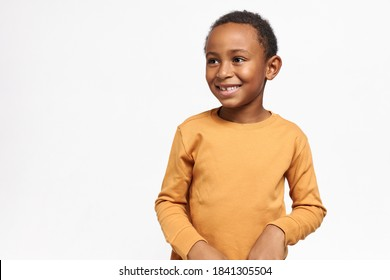 Cute Afro American schoolboy in yellow sweatshirt posing against white wall background with copy space for your information, smiling, expressing positive emotions. Human emotions and feelings