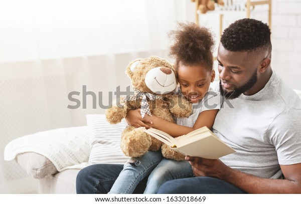 Cute afro family father and daughter reading book, sitting on couch at home, copy space