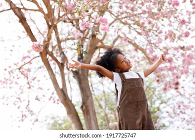 A cute Afro girls under flowering tree in park.