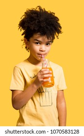 Cute afro little boy drinking orange and carrot juice from a bottle with a straw. Isolated on yellow