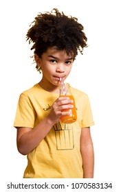 Cute afro little boy drinking orange and carrot juice from a bottle with a straw. Isolated on white