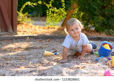 Cute alert little baby boy crawling in sand in a playground surrounded by his plastic toys as her smiles happily at the camera