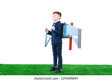 Cute ambitious little kid in suit getting ready to fly with jet pack wings, Big dreams and success concept