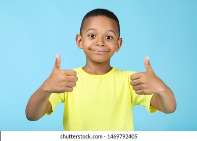 Cute american boy showing thumb up on blue background