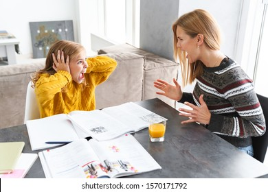 Cute angry little girl doing homework with her mom while sitting at the table at the living room, having an argument