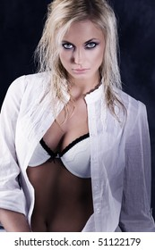 cute ans sexy blond girl in a fashion shot wearing an open white shirt showing bra. strong contrast