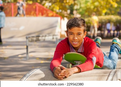 Cute Arabian boy laying on green skateboard