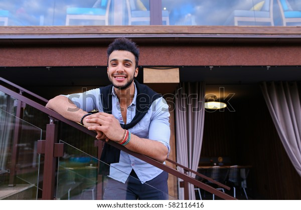 Cute Arabian businessman student posing for catalog of brand of men's clothing, went to restaurant for lunch, after work, made an appointment with friends, smiling and enjoying life. Handsome Muscular