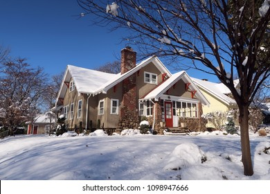Cute arts & crafts bungalow style house on a winter day. Snow on the ground.