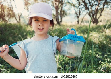 Cute Asain girl catching butterfies with a net and holding a box of insects, outdoor activity for kid, homeschooling montessori education and learn through play concept