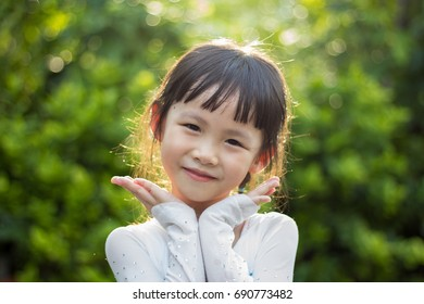 Cute asia kid smile in the garden with nice green bokeh
