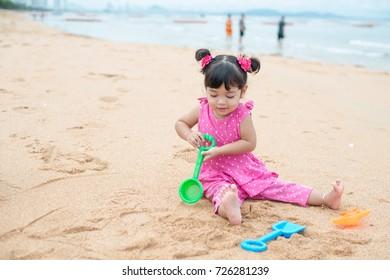 cute Asia little girl play with sand on beach