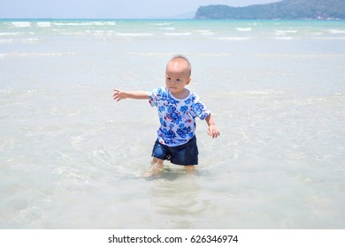 Cute Asian 1 year old toddler baby boy child standing / playing on white sand beach ,Family travel, water outdoor activity on summer beach vacation with children,Thailand, Selective focus, cool tone