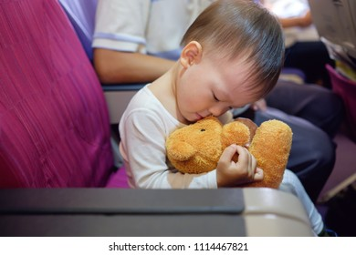 Cute Asian 2 years old toddler boy child hugging loving & kissing teddy bear stuffed toy friend during flight on airplane, Flying with children, Happy air travel & little traveler concept, Shallow DOF