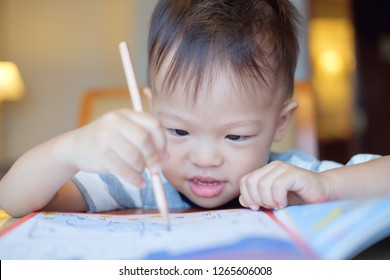 Cute Asian 2 years old toddler boy writing / drawing with pencil, Preschooler doing homework, Creative play for toddler, Little kid prepare for preschool admission test, improve focus in child concept