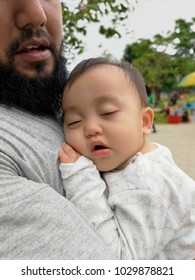 Cute asian 8 month old baby girl sleeping on father's chest in the park. Bearded father cuddling baby with tenderness. Selective focus.