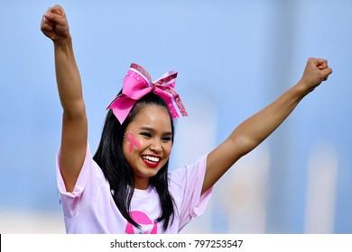 Cute Asian American Cheerleader performing at a High School Football Game