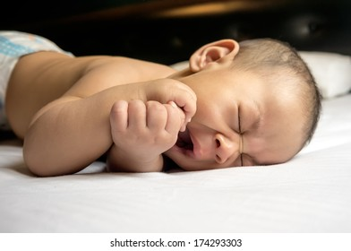 Cute Asian baby boy on white bed yawning