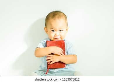 Cute asian baby boy read on a Holy Bible for faith and bible study and teach kid in the way of GOD.Concept for faith, spirituality and religion.
