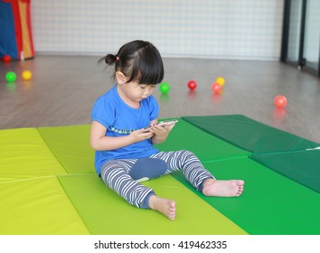 Cute asian baby girl age about one year old and nine month playing a smartphone at the Kid room
