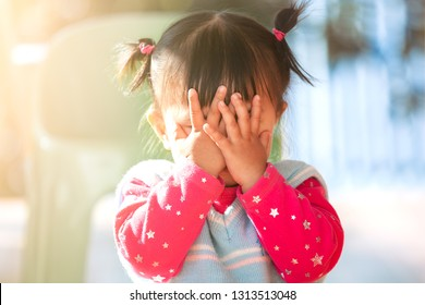 Cute asian baby girl closing her face and playing peekaboo or hide and seek with fun
