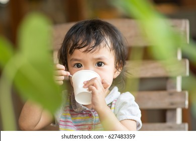 Cute asian baby girl drinking water by paper cup