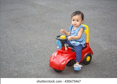 Cute asian baby girl drive a car toy in the park